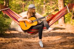 Woman in hat play guitar and relaxing in hammock hanging among pine trees in background. Camping rest concept stock images