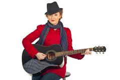 Woman with hat playing guitar Royalty Free Stock Photography