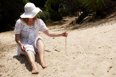 The woman in a hat playing with sand Royalty Free Stock Photo