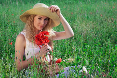Woman in hat with poppy bouquet Royalty Free Stock Image