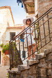 Woman in hat posing on beautiful stairs at narrow street Stock Photography