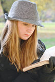 Woman in hat reading. Young woman in hat reading book in autumn park closeup Royalty Free Stock Photo