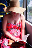Woman in hat reading book on train bus Stock Image
