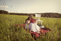Woman with Hat is Reading on Picnic Blanket. Woman with Hat in White Dress is Sitting on Red Blanket on Green Meadow with White Chair and Picnic Basket Stock Image