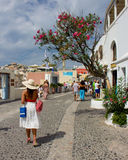 Woman with hat rear view walking. Young woman wearing a hat and white skirt walking alone in a pedestrian street in Santorini, Greece Stock Photography