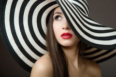 Woman in a hat and with red lips. Portrait of a young beautiful brunette. Dark background stock images