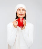 Woman in hat with red tea or coffee mug Stock Photo