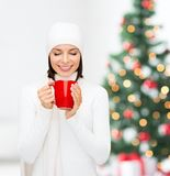 Woman in hat with red tea or coffee mug Royalty Free Stock Photos