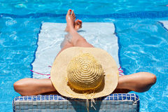 Woman in hat at relaxation on holidays. Woman in hat relaxing at swimming pool bed Royalty Free Stock Photo