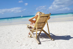 Woman in hat relaxing on beach on a deck chair Stock Photo