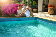 Woman in hat relaxing near luxury swimming pool Royalty Free Stock Image
