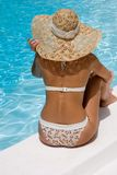 Woman in hat relaxing beside pool Stock Photo