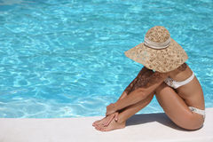 Woman in hat relaxing beside pool Royalty Free Stock Photo