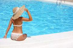 Woman in hat relaxing beside pool Royalty Free Stock Photos