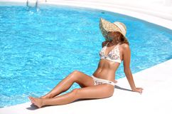 Woman in hat relaxing beside pool Stock Image