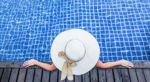Woman in hat relaxing at the pool stock images