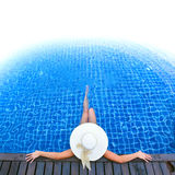 Woman in hat relaxing at the pool Stock Photography