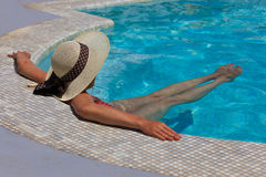 Woman in hat relaxing at the pool Stock Photo