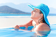 Woman in hat relaxing in swimming pool Stock Photos
