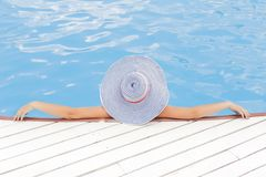 Woman in hat relaxing in swimming pool Stock Image