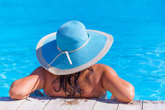 Woman in hat relaxing at swimming pool royalty free stock image