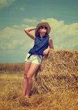 Woman with hat resting on a bale of straw Stock Photos