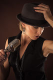 Woman in a hat with a retro microphone Royalty Free Stock Image