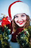 Woman in and hat of Santa with a christmas ball Royalty Free Stock Photography