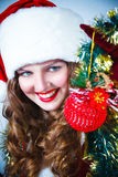 Woman in and hat of Santa with a christmas ball Royalty Free Stock Images