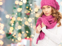 Woman in hat and scarf over christmas tree lights Royalty Free Stock Photo