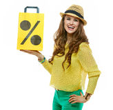 Woman in hat showing shopping bag symbolising beginning of sales Stock Image