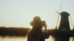 Woman in hat sits on sunset countryside lake quay. Girl takes an old windmill photo using her smartphone. 4K back view. stock video footage