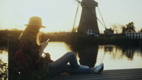 Woman in hat sits on sunset lake pier Netherlands. Female blogger with smartphone and camera takes a windmill photo. 4K. stock footage