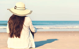 Woman in a hat sitting on the beach Stock Image