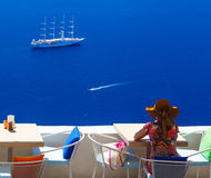 Woman in hat sitting in cafe and enjoys views of sailing cruise ship, Santorini, Fira, Greece royalty free stock photo