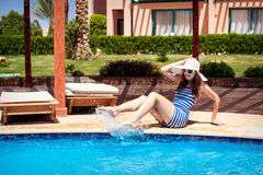 Woman in a hat sitting on the edge of the pool Stock Images