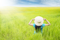 Woman with hat sitting on the green meadow Stock Photography