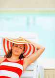 Woman in hat sitting laying on chaise-longue. Portrait of relaxed young woman in hat sitting laying on chaise-longue stock image
