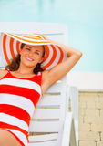 Woman in hat sitting laying on chaise-longue Stock Image