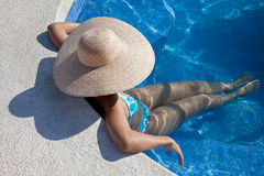 Woman with hat sitting in the pool Stock Photography