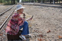 Woman in hat sitting on a suitcase. Boho style woman in hat sitting on an old vintage suitcase at a railway station, holding a mobile phone. Profile view Royalty Free Stock Photography