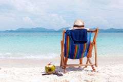 Woman in hat sitting on tropical beach Stock Image