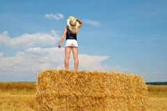 Woman with hat standing on a bale of straw Royalty Free Stock Image