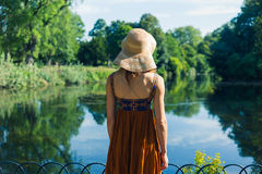 Woman in hat standing by pond in park Stock Photos