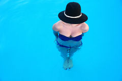 Woman with hat standing in swimming pool Stock Image