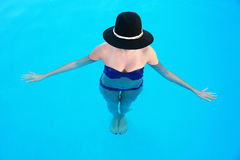 Woman with hat standing in swimming pool Stock Photography