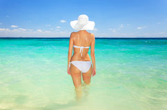 Woman in hat standing on the tropical beach Stock Photo