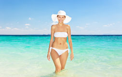 Woman in hat standing on the tropical beach Stock Photos