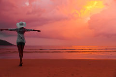 Woman in hat standing on wet sand on beach Stock Images