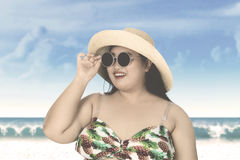 Woman with hat and sunglasses at coast Stock Photo
